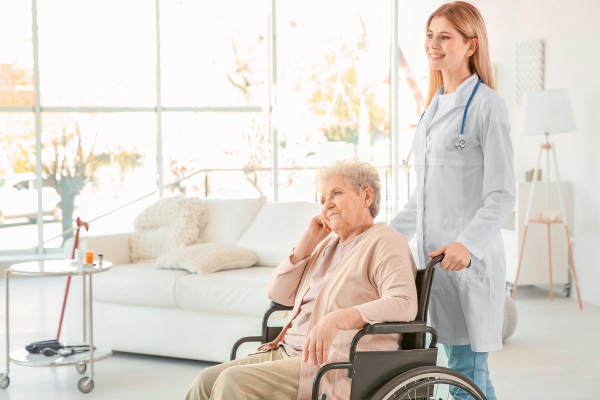 Ärztin und ältere Dame im Rollstuhl